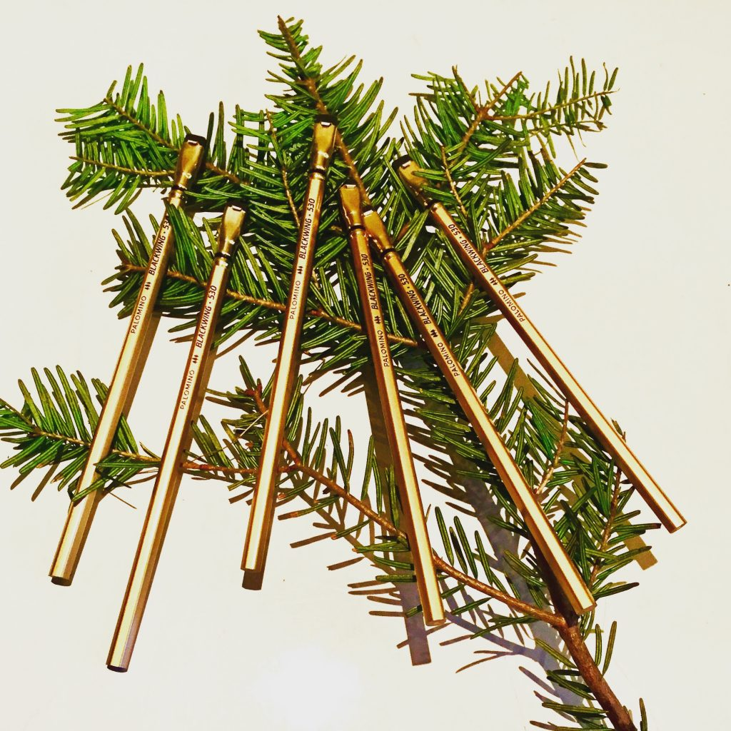 Some golden pencils on a Christmas tree twig