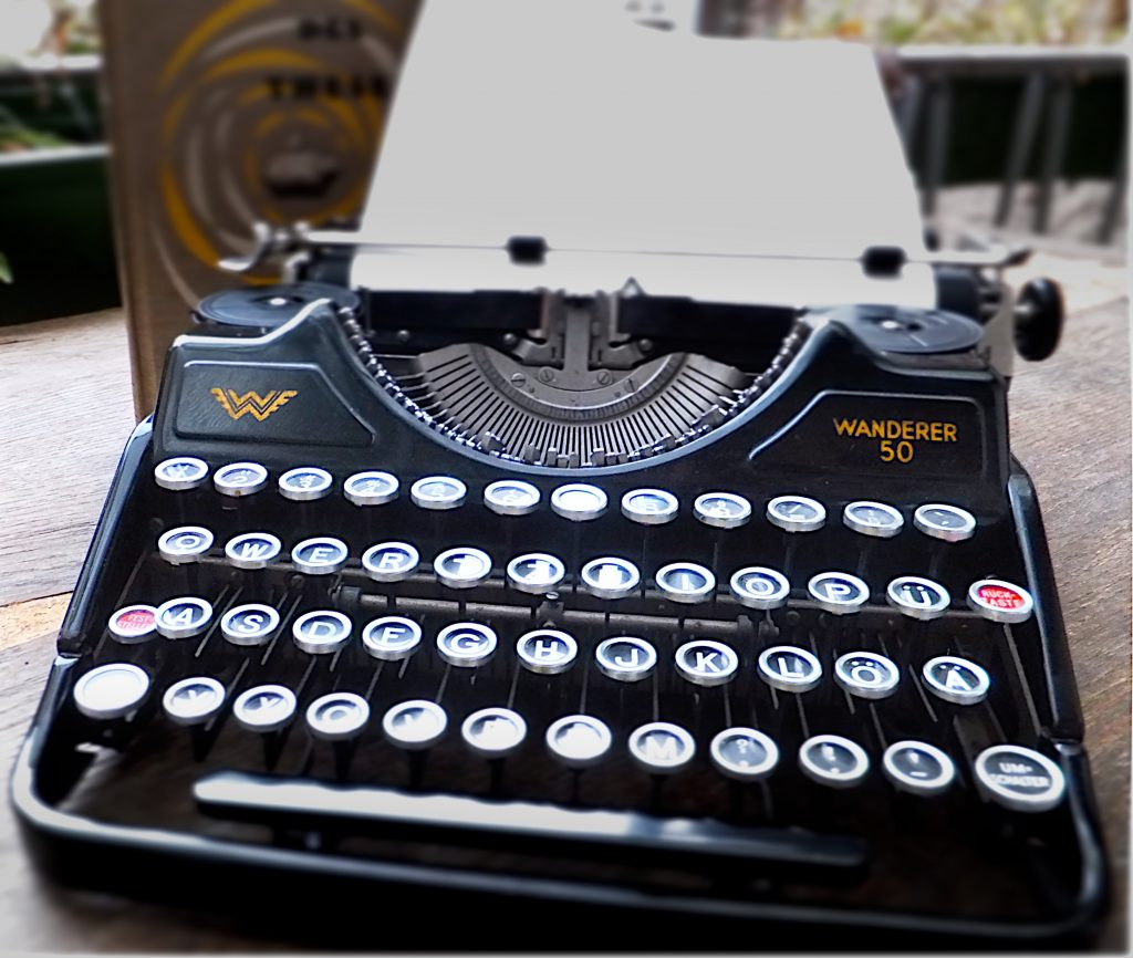 An old black typewriter on a wooden table