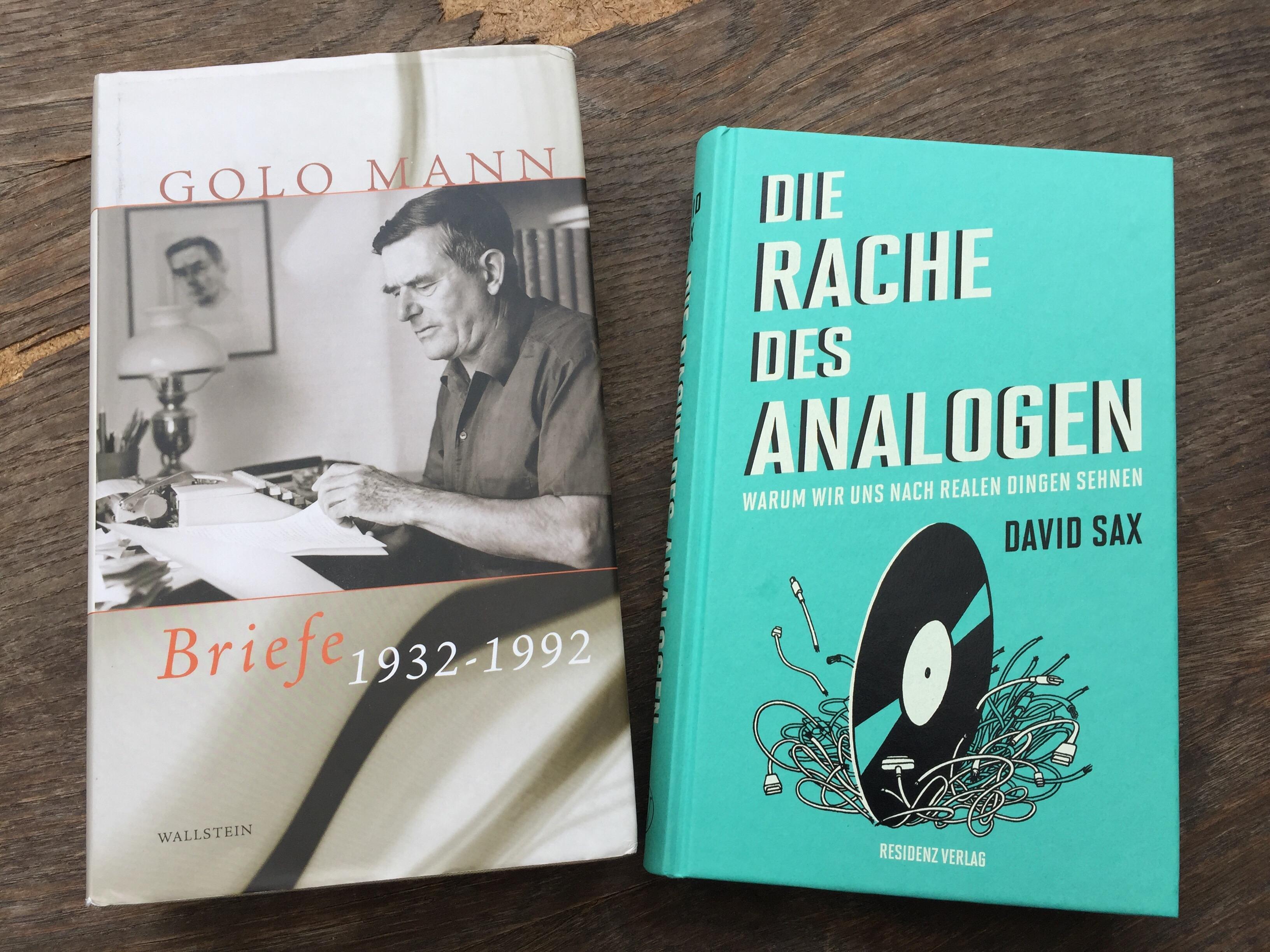 Zwei Bücher liegen auf einem Holztisch