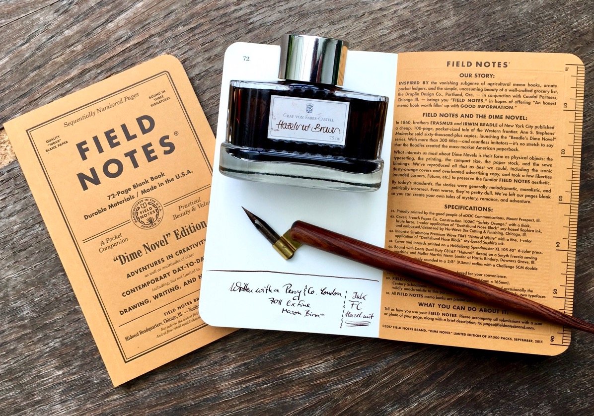 A Field Notes Copybook, a glass of ink and a nib on a table