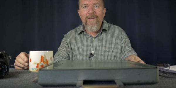 Screenshot von Joe Van Cleave, der eine sehr flache Schreibmaschine vor sich auf dem Tisch liegen hat