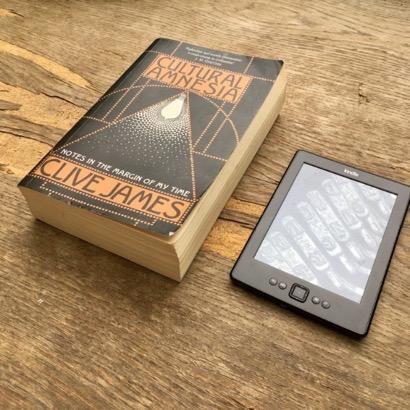 Ein dickes Taschenbuch liegt neben einem eReader