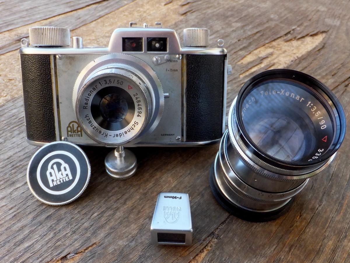 Ein alter Foto-Apparat Akarette II, ein Tele-Objektiv und ein kleine Sucher auf einem Tisch