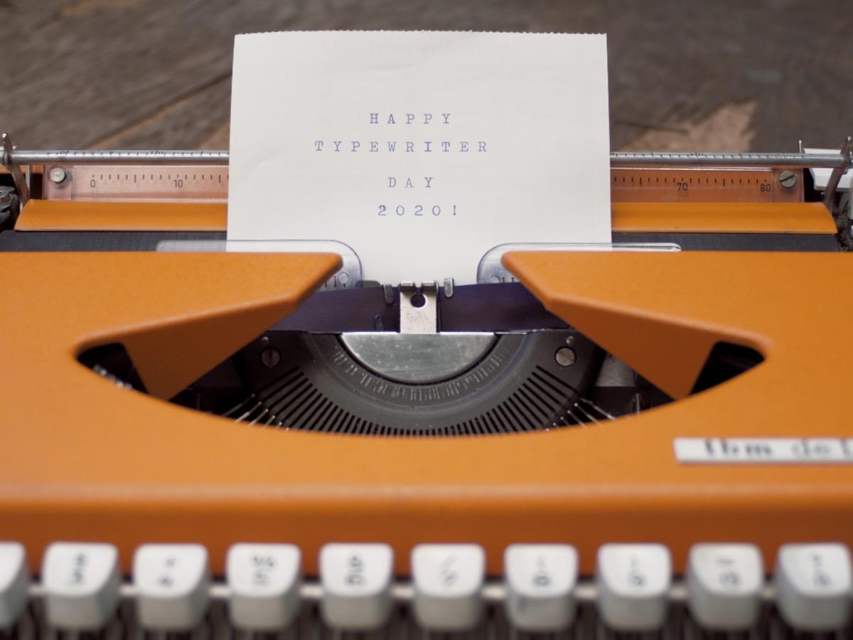 Nahaufnahme einer orangen Schreibmaschine, auf einem eingespannten Zettel steht Happy Typewriter Day 2020