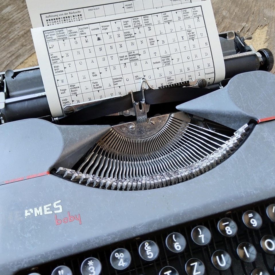 Teilansicht einer mechanischen Schreibmaschine, in der ein ausgfülltes Kreuzworträtsel eingespannt ist